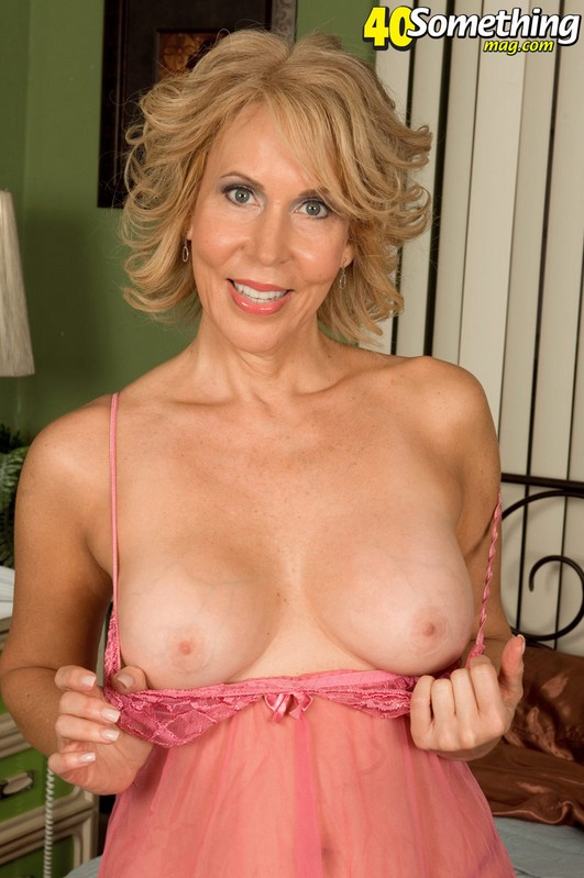 Blonde mature Erica Lauren taking off her pink lingerie and showing