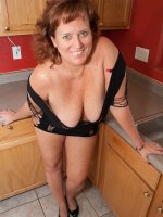 Busty Dawn Marie shows her bib tits in sexy black dress in the kitchen