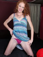 Redhead MILF Ande masturbating with purple toy.