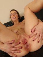 Blond MILF Luci Angel masturbating on the black sofa.