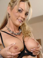 Busty blonde MILF Sindy Lange spreads her pink pussy lips.