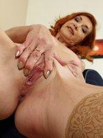 Older redhead Ariel spreads her pussy lips wide open.