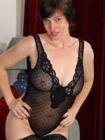 Short-haired brunette MILF in black lingerie displays her superb body
