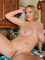 Busty blonde housewife shows her superb body in the kitchen