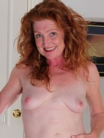 Mature redhead takes off her elegant black dress and displays her shaved pussy