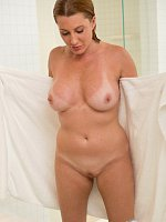 Tanned busty blonde washes her sexy body