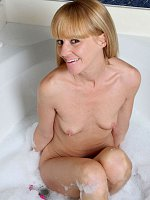 Older mom with tiny tits plays with dildo in a bathroom