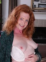 Older redhead Veronica Smith strips naked on the desk.