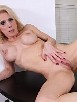Busty blond cougar Jodie Stacks fingers her pussy.