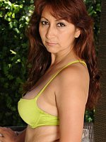 Curvy mature redhead Estella Eves strips naked outdoors.
