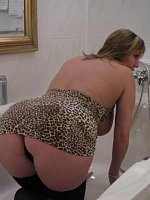 Busty MILF shows long legs and round ass doggy style in the bathtub