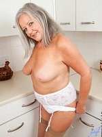 Mature lady plays naked in the kitchen