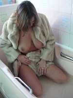 MILF in fur coat lies in the bathtub