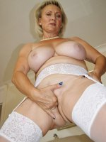 Busty blonde in stockings plays with her shaved pussy